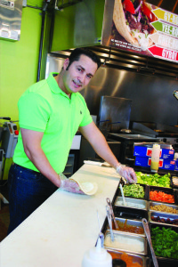 Hassan Atarmal makes a gyro in Fresh Mediterranean Express, the restaurant he and wife, Jeni Betts, own and operate in Waukee. Photo by Melissa Walker